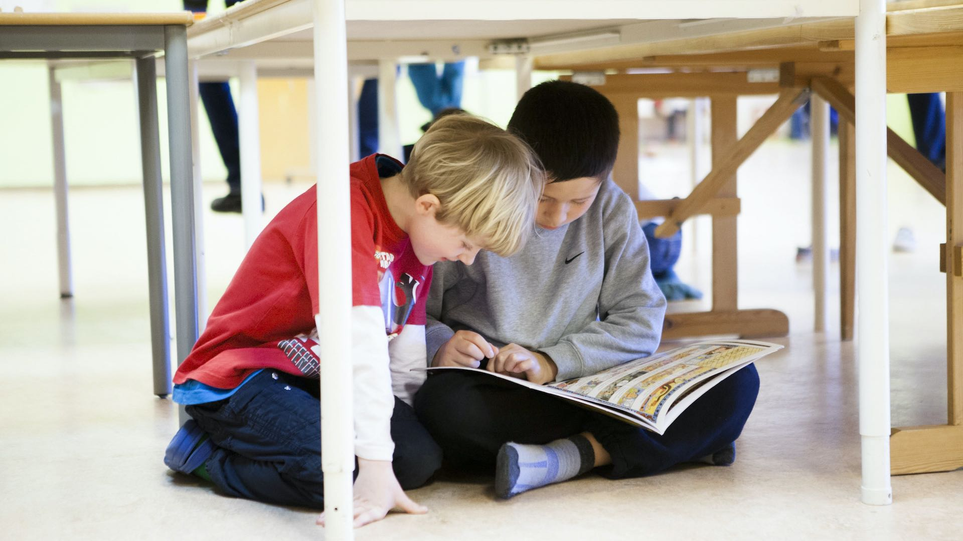 Two young students sitting reading under a table at Arendal International School
